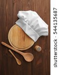 Small photo of Chef hat, cutting board and kitchenware on wooden background
