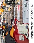 Small photo of Many colorful electric guitars aligned in a store showroom, body detail