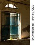 Small photo of Old blue door is ajar, and through the slit pouring sunlight.