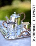 Small photo of Table set for an English high tea, or afternoon tea, outside with silver teapot and linen tablecloth
