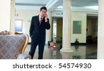 Young businessman making a mobile call in hotel lobby - stock photo