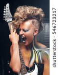 Small photo of Portrait of aggressive punk with guitar. Stylish woman screaming while performing with guitar, bright rocker look with body art and hairstyle. Subculture, expression, courage, drive, lifestyle concept