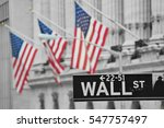 A Wall Street Sign In Front Of...