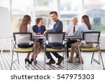 smiling businessman sitting at... | Shutterstock . vector #547975303