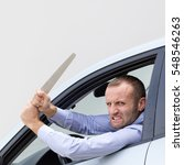 Small photo of Aggressive and violent driver armed with a big kitchen knife. Copy space on the gray background.