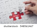 Small photo of Hand holding piece of jigsaw puzzle with word budget 2017.