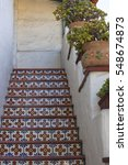 Small photo of Multi colored mexican tile on steps in a stairwell of an adobe building