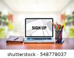 Small photo of Open laptop with isolated white screen on old wooden desk with text SIGN UP