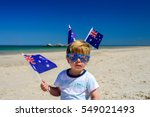 Small photo of Cute smiling kid with Australian flags sitting on the sand at the beach on Australia Day