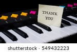 Small photo of Black and white piano keys, words on paper sticker thank you