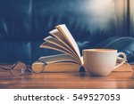 Small photo of Cup of coffee with glasses and book on table in afternoon time