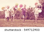 Small photo of Happy girls and boy running all together with multicolored balloons in backyard