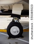 Small photo of High detailed closeup view on aircraft wheels. Aircraft on the ground in sunny day, airshow
