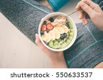 Small photo of Young woman is resting and eating a healthy oatmeal after a workout. Fitness and healthy lifestyle concept.