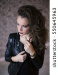 Small photo of Punk rock style or halloween make-up. Fashion woman model face with bright glamour makeup. Perfect skin, black gloss eyeshadows on eyes and dark brown glossy lips visage.