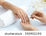 Small photo of Nail Salon. Closeup Of Beautician Hands Cleaning Female Client's Nails With Orange Wooden Stick, Cuticle Pusher, Removing Cuticles In Beauty Salon. Woman Hands Nail Care And Manicure. High Resolution