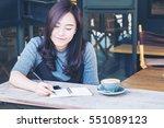 a beautiful asian woman writing ... | Shutterstock . vector #551089123