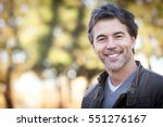 Stock photo handsome mature happy man smiling at the camera outside 551276167