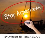 Small photo of Woman Hand Writing Stop Aspartame with a marker over transparent board. Isolated on Sunset Boat. Business concept. Stock Photo