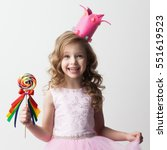 Small photo of Beautiful little candy princess girl in crown holding big lollipop and smiling