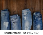 Four Blue Jeans On Wooden...