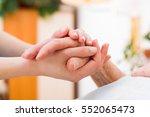 nurse holding the hand of an... | Shutterstock . vector #552065473