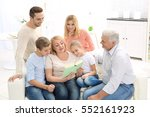happy family reading book while ... | Shutterstock . vector #552161923