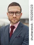 Small photo of Stern stylish young businessman wearing glasses staring intently at the camera with a troubled frown, close up head and shoulders