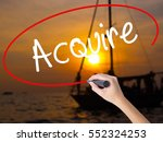 Small photo of Woman Hand Writing Acquire with a marker over transparent board. Isolated on Sunset Boat. Business concept. Stock Photo