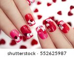 Small photo of Nail designs with different sequins in the shape of hearts on red and pink nails for girls.