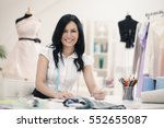 Small photo of Smiling fashion designer working at her desk.