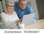 senior couple at home using... | Shutterstock . vector #552964657