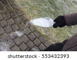 Small photo of Man scattering salt in winter for de icing