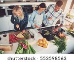 three friends cooking at... | Shutterstock . vector #553598563