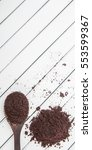 Small photo of Dried super food acai berry powder in wooden spoon over wooden background