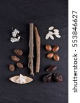 Small photo of Composition of shea butter and nuts, argan fruits and seed on a black background. Flat lay