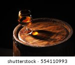 Glass Of Cognac With Barrel On...