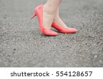 Stock photo coral pink heels posed on gravel road 554128657