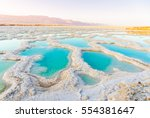 Stock photo view of dead sea coastline salt crystals at sunset texture of dead sea salty sea shore 554381647