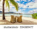 two chairs and table on a sand...   Shutterstock . vector #554389477