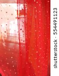 Small photo of Red color of aflutter fabric with light through