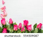 Stock photo pink rose on white wooden background 554509087