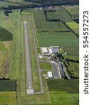 Small photo of 30 August 2016, Stadlohn, Germany. Aerial view of Airport Flugplatz Stadlohn Vreden. It's a small airstrip with a tower and a concrete runway in the middle of green fields.