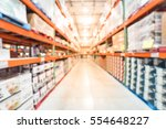 Small photo of Blurred image large warehouse with row of aisles and shelves from floor to ceiling with bin number. Defocused background of industrial distribution interior aisle, inventory, hypermarket, wholesale.