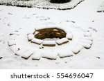 Small photo of Fire pit made of the yellow aluminous bricks surrounded by pebble covered with the first snow in the late autumn garden