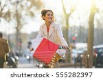 young woman riding bicycle in... | Shutterstock . vector #555282397