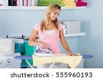 smiling woman ironing clothes... | Shutterstock . vector #555960193