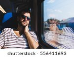 young man traveling on a train... | Shutterstock . vector #556411693