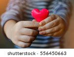child holding a small pink... | Shutterstock . vector #556450663