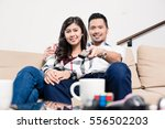 Asian couple on sofa in living room changing tv channel